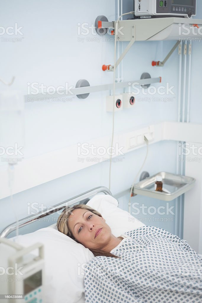 Female patient looking at camera while lying on a bed royalty-free stock photo