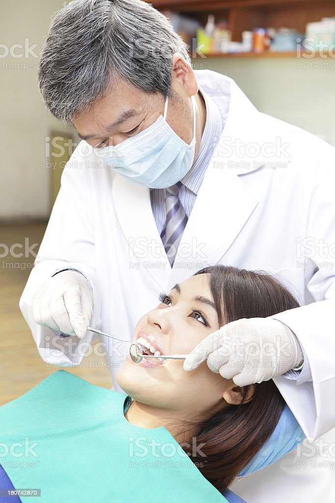 Female patient with dentist and assistant in a dental treatment royalty-free stock photo