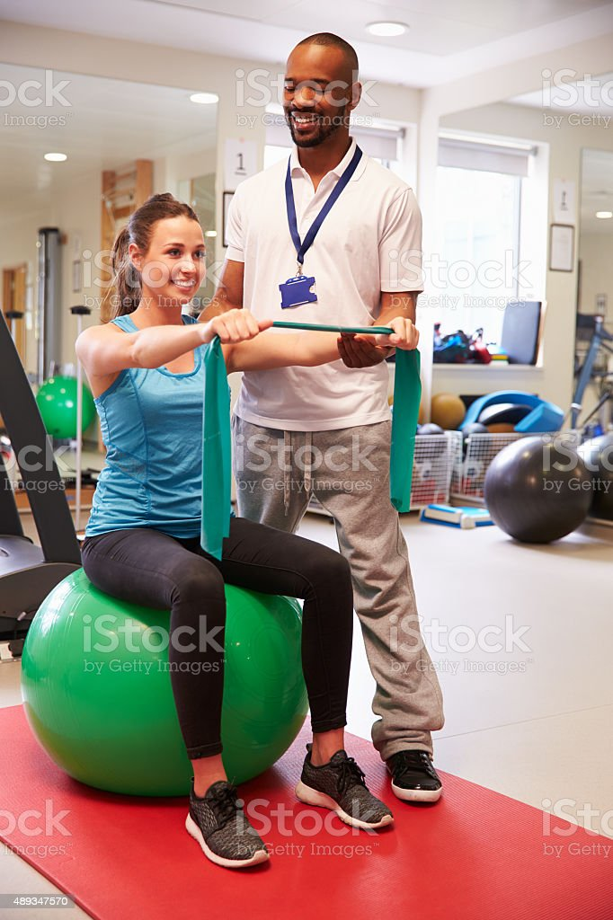 Female Patient Working With Physiotherapist In Hospital stock photo