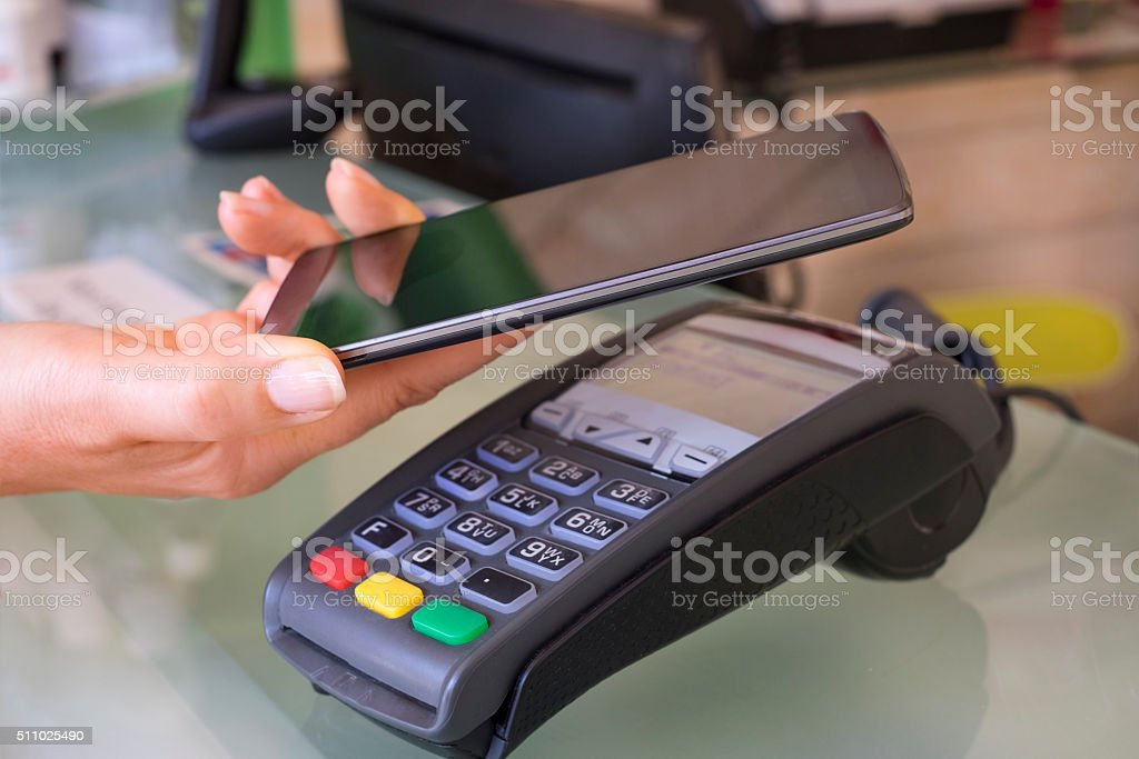 Female paying with NFC technology on mobile phone, beautician stock photo