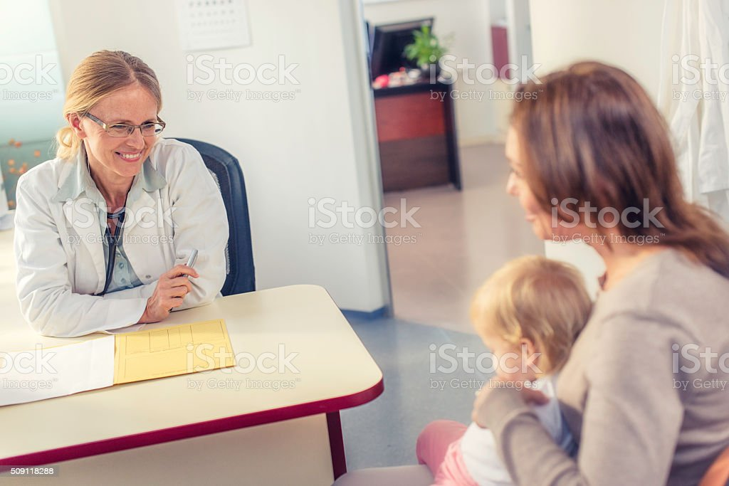 Female pediatrician with her little patient stock photo