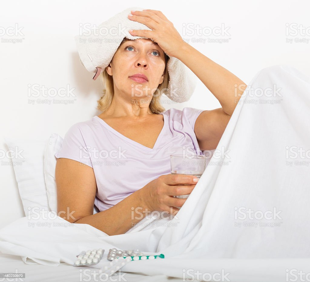 female pensioner laying   with headache stock photo