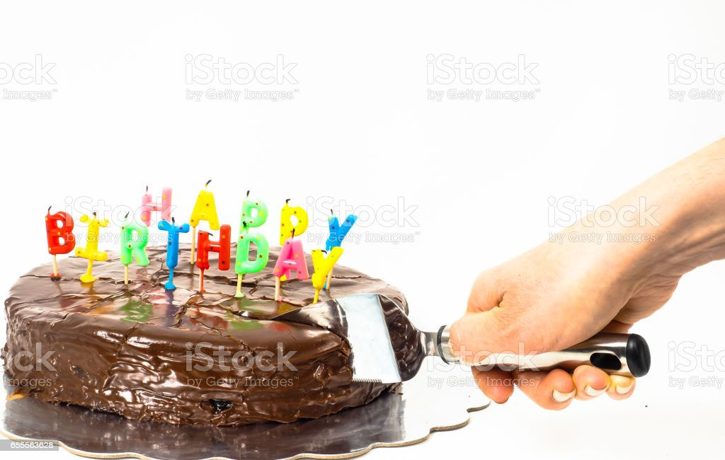 Female person cutting a homemade sachertorte, with birthday candles stock photo