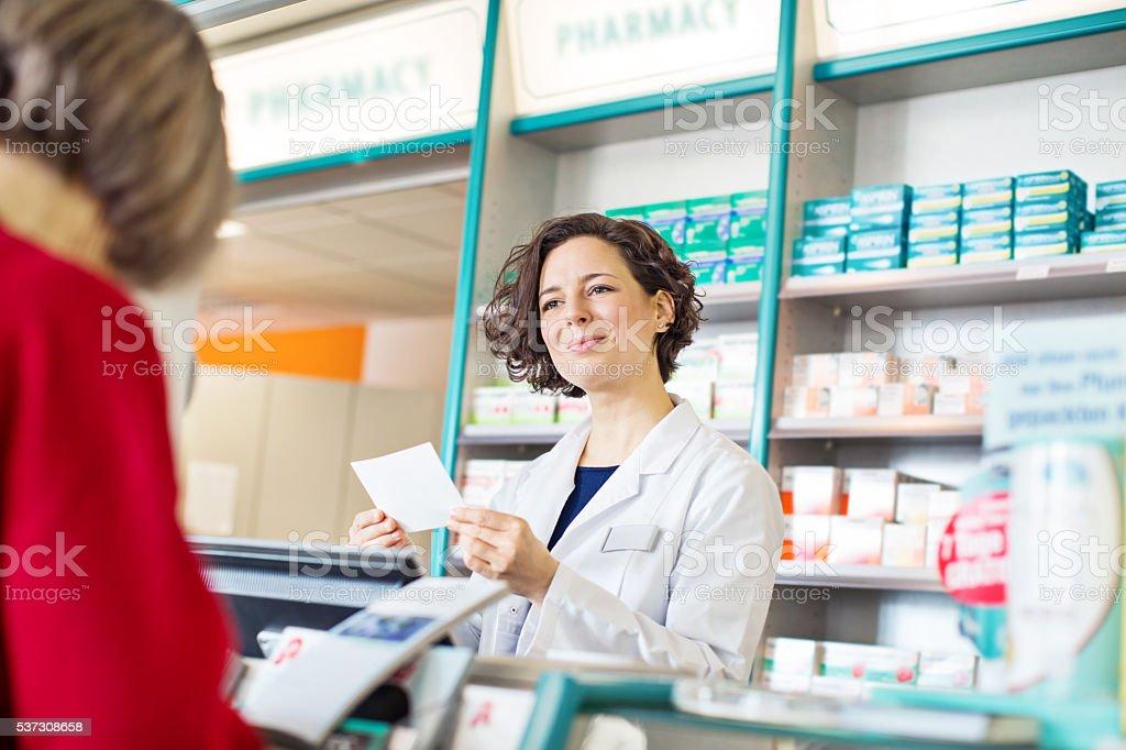 Female pharmacist assisting to customer in pharmacy stock photo