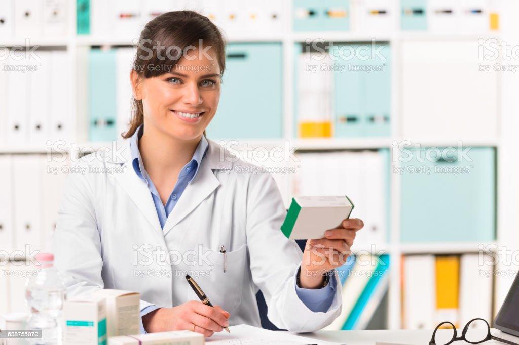 Female pharmacist sat at desk writing notes stock photo