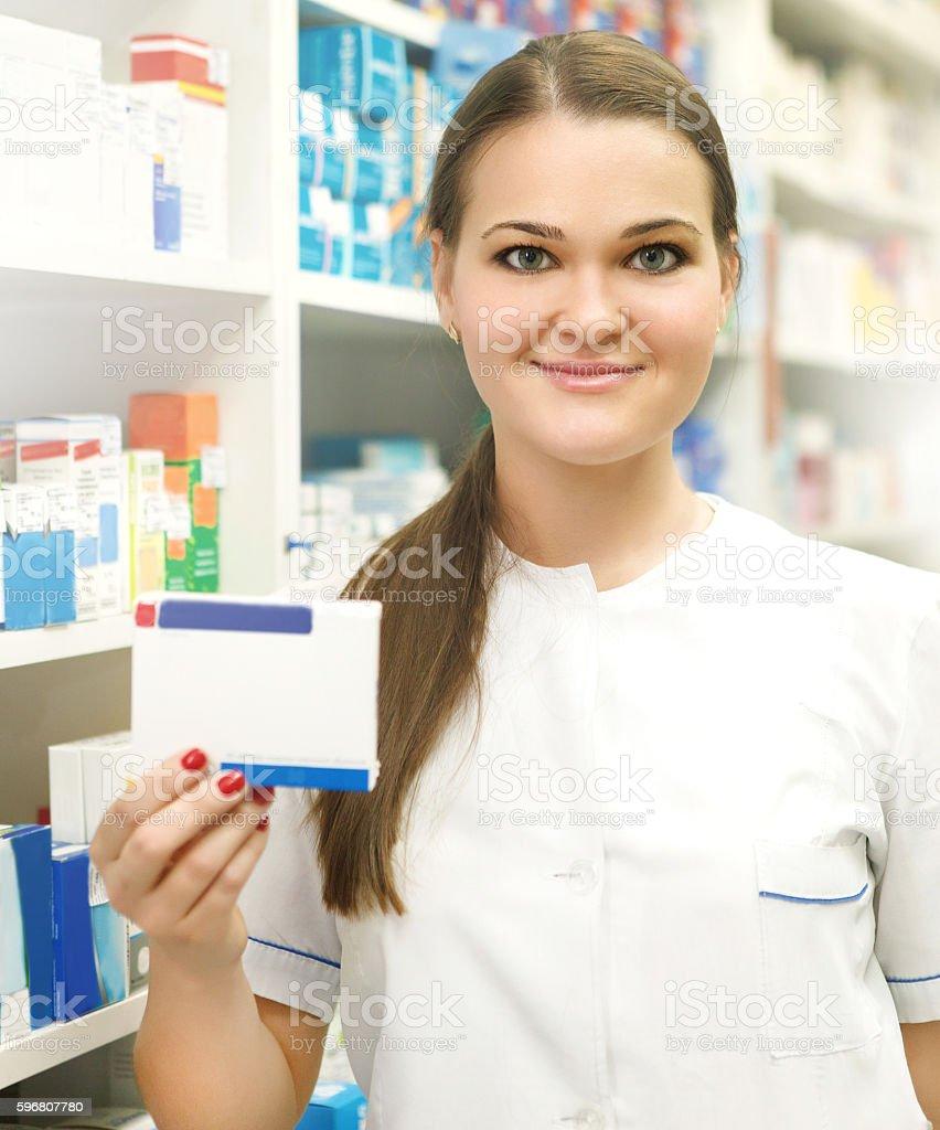 Female pharmacist showing medicine box at pharmacy counter stock photo