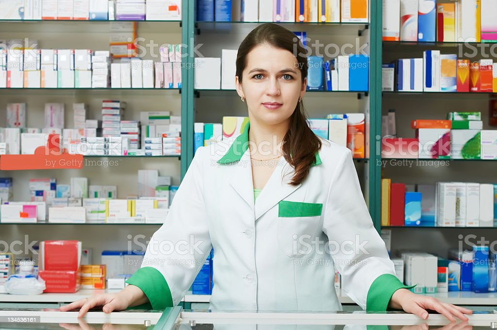 Female pharmacist standing behind counter royalty-free stock photo