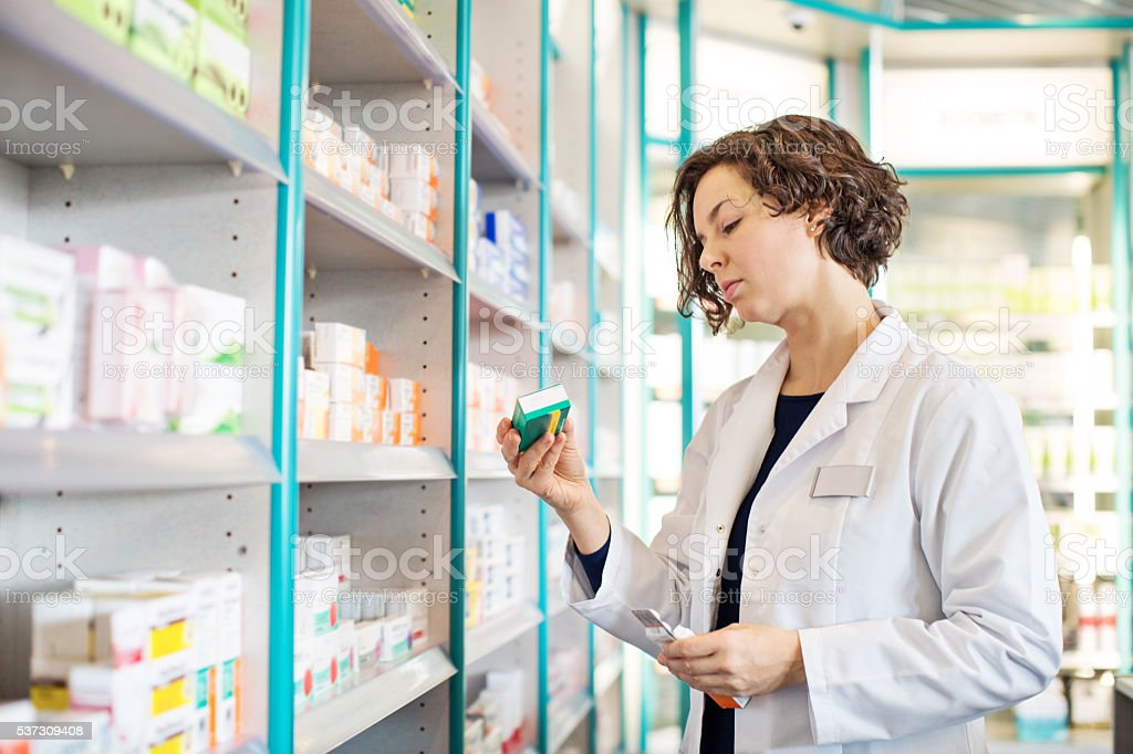 Female pharmacist taking medicine from shelf stock photo