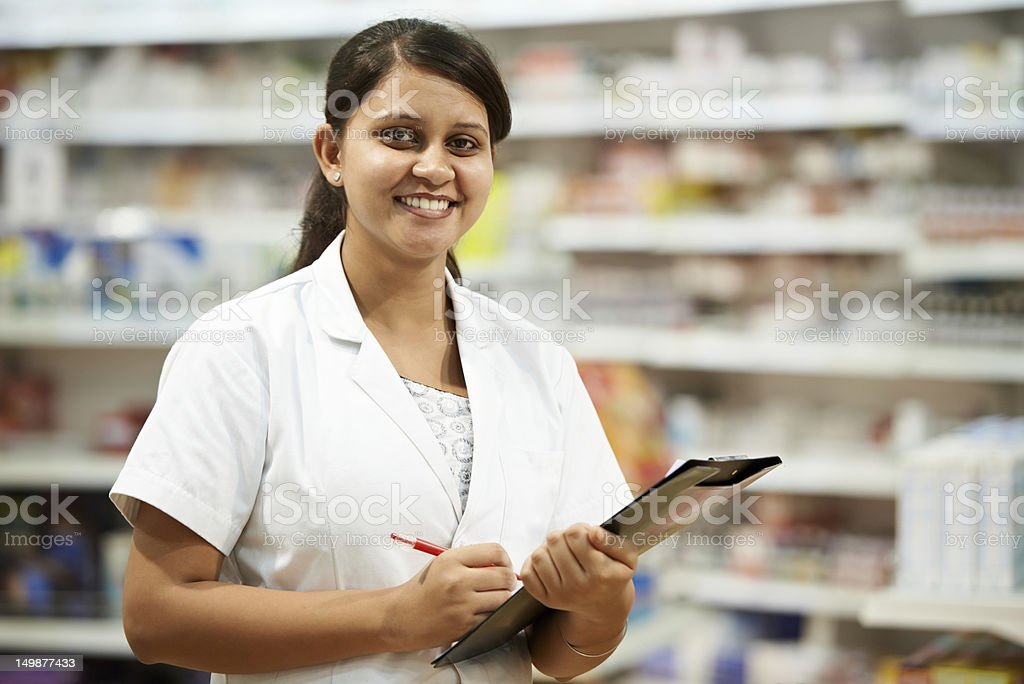 Female pharmacist with a clipboard in a drugstore pharmacy royalty-free stock photo