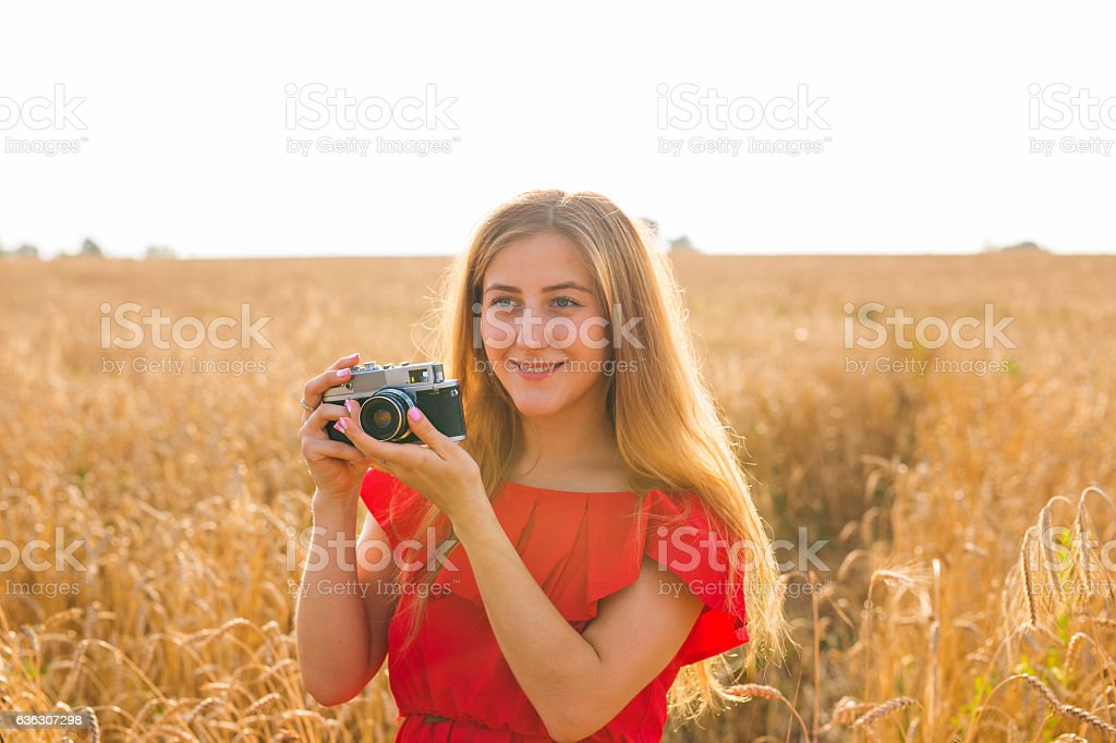 female photographer in the field with a camera taking pictures stock photo