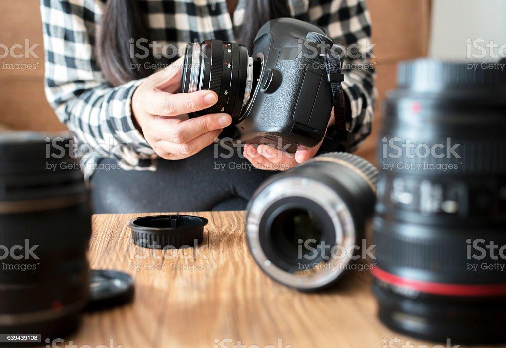 female photographer placing lens on camera