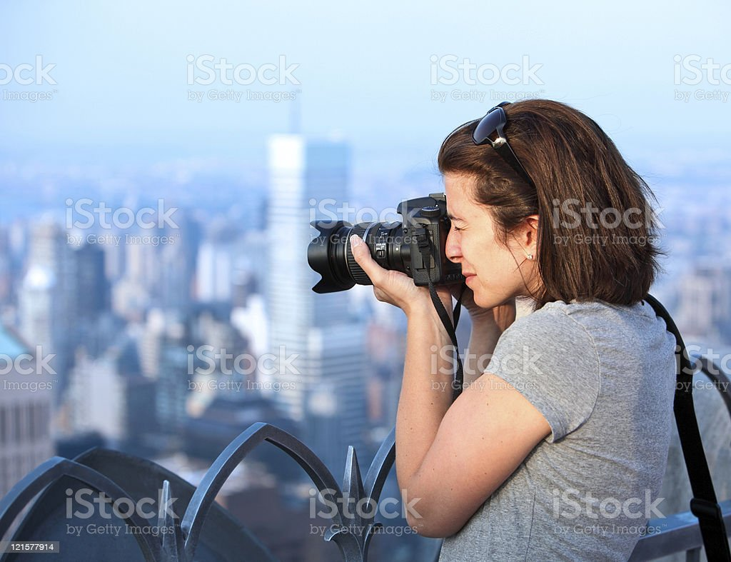 Female photographer taking a picture of a city from up high royalty-free stock photo