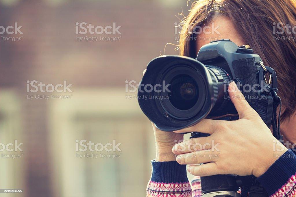 Female photographer taking photos using dslr stock photo