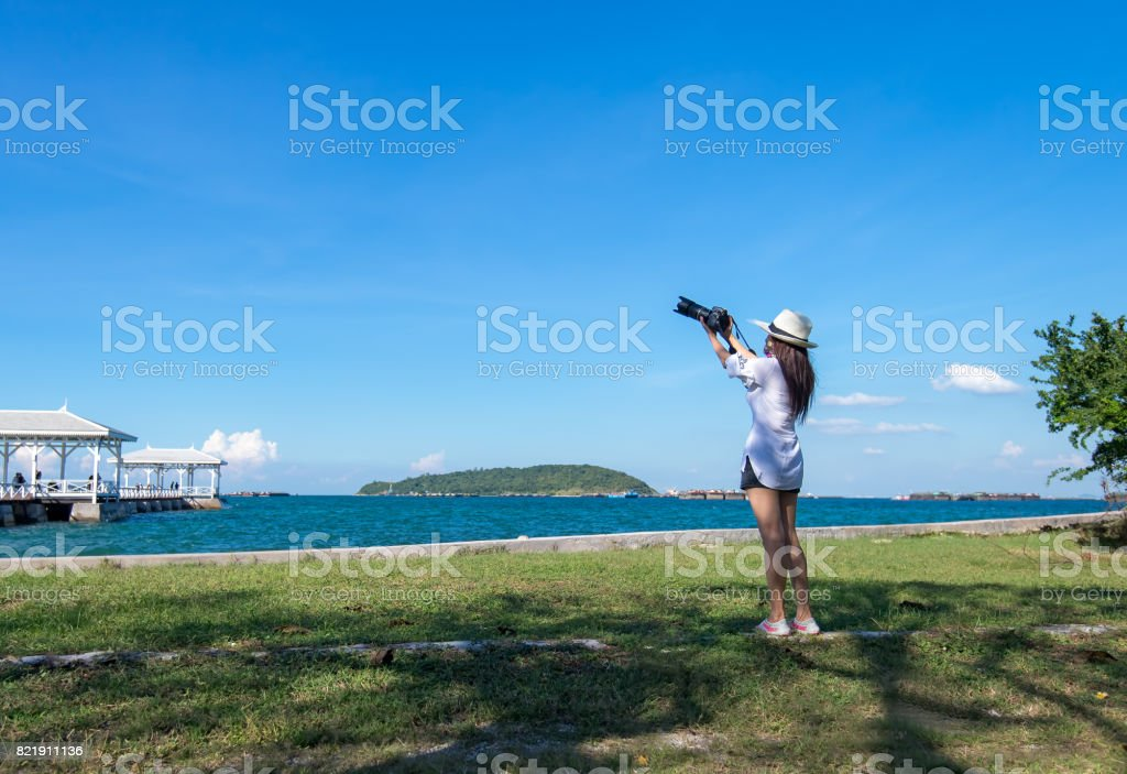 Female photographer taking pictures of the beautiful beach and blue sky stock photo