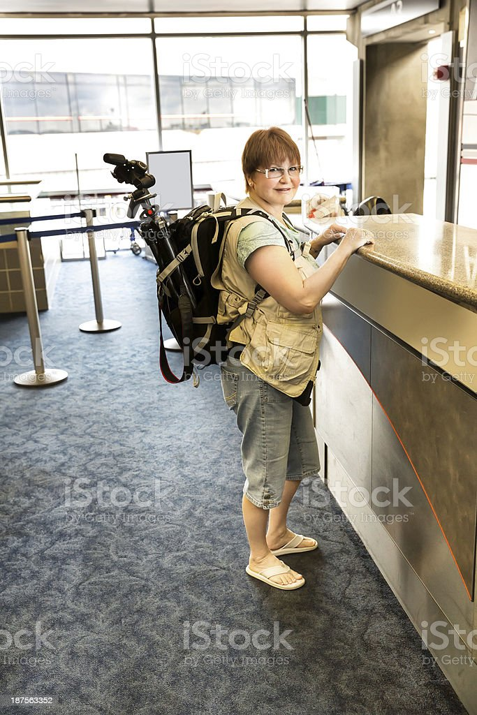 Female Photographer waiting for assistance at airline counter royalty-free stock photo