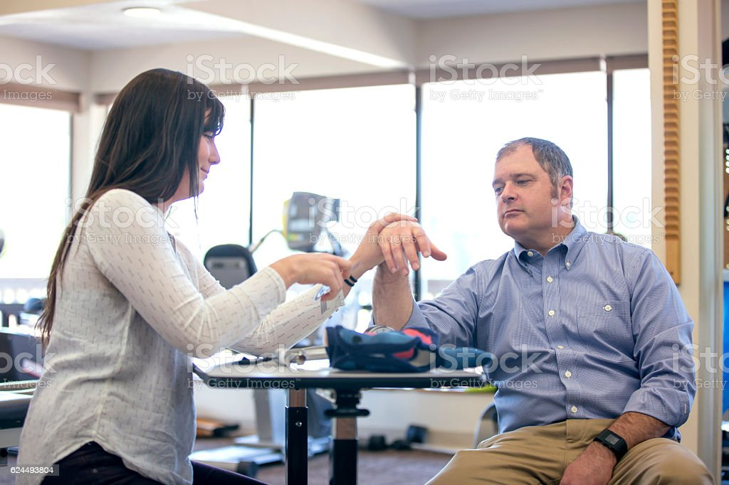 Female physical therapist adjusting adult male wrist during rehab stock photo