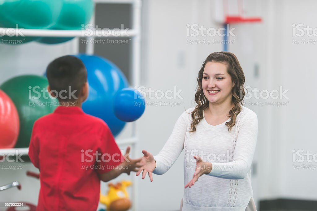 A female physical therapist doing rehabilitation with a child patient stock photo