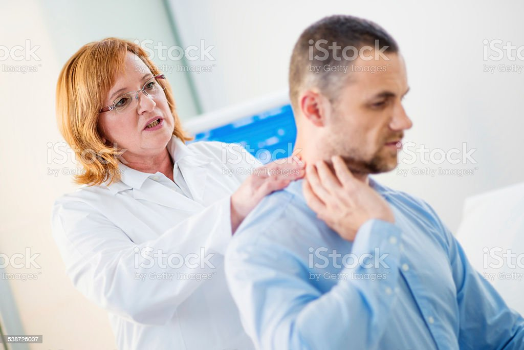 Female Physical Therapist Examines the Patient's Neck stock photo