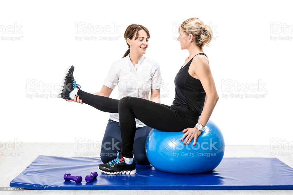 Female physical therapist helps patient in exercises for knee stock photo