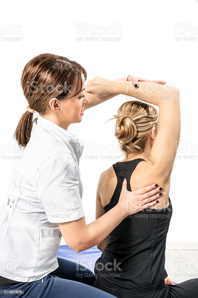 Female physical therapist treating patient's shoulder and back stock photo