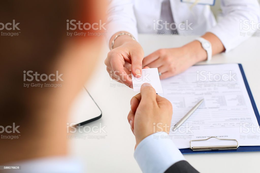 Female physician hand hold white blank calling card stock photo