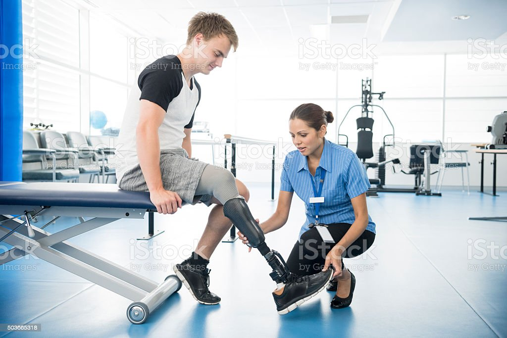 Female physiotherapist helping young man with prosthetic leg stock photo