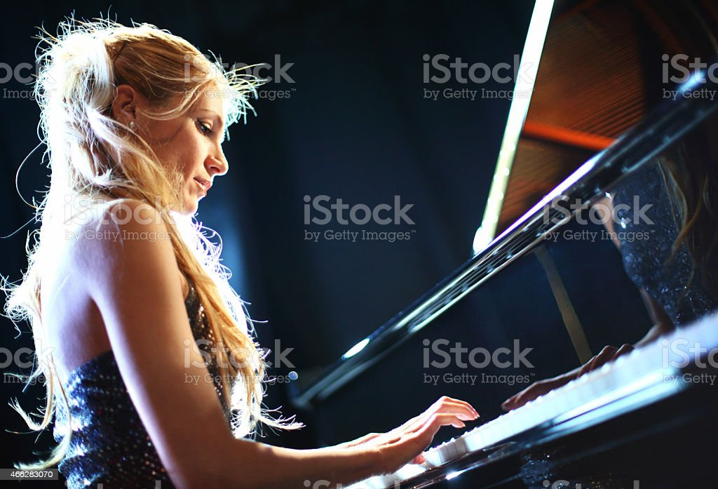 Mid-aged blond woman playing piano in concert.She\'s wearing elegant...