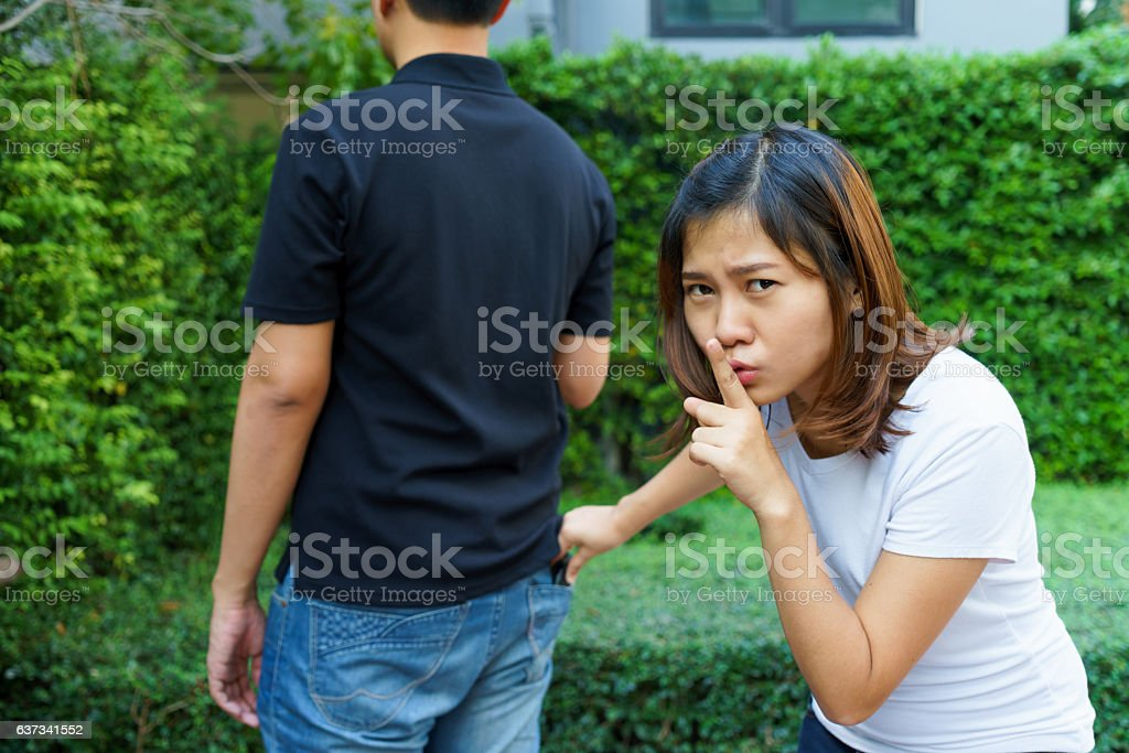 Female pickpocket stealing a wallet from behind pocket on jeans stock photo