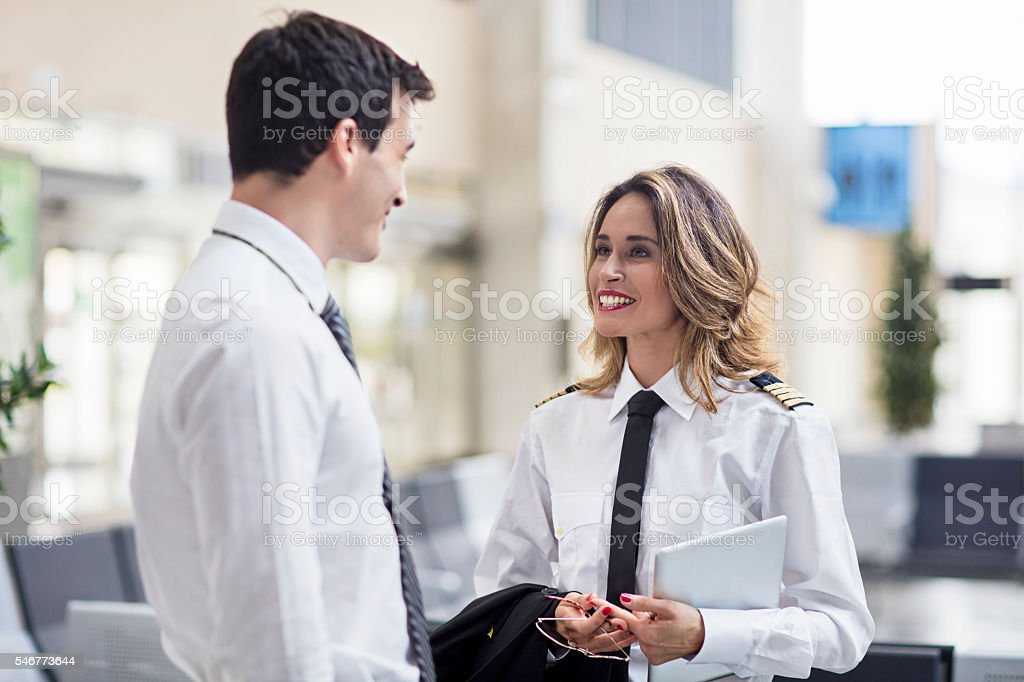 Female pilot and flight attendant man talking in the airport stock photo