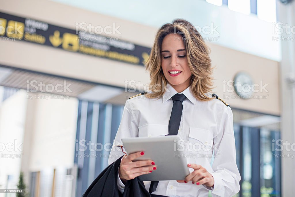 Female pilot using digital tablet in the airport stock photo