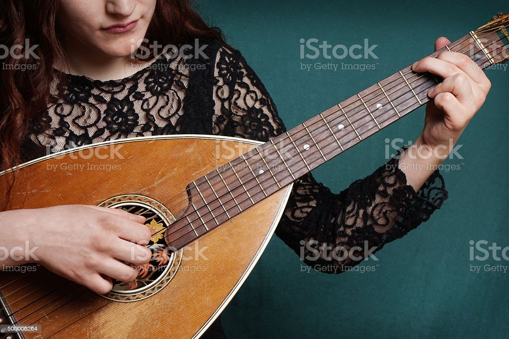 female playing lute string instrument stock photo