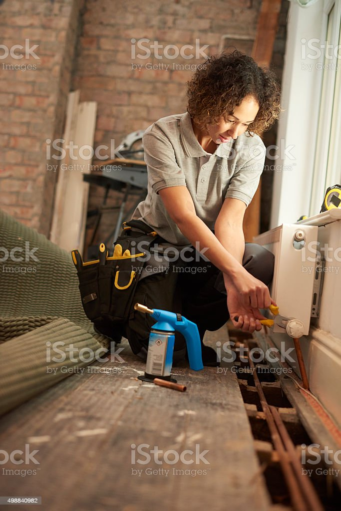 female plumber radiator installation stock photo