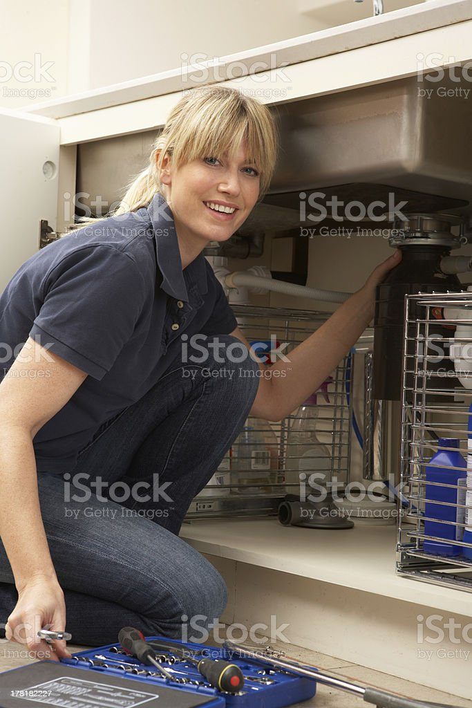 Female Plumber Working On Sink In Kitchen royalty-free stock photo