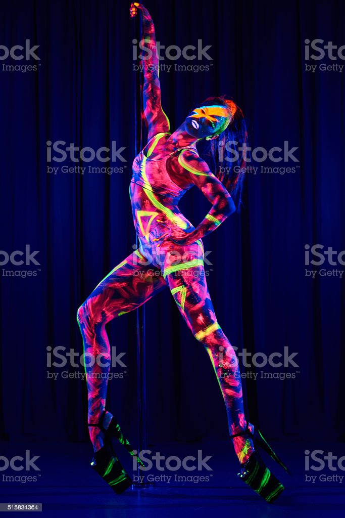 Female pole dancer in neon colours under ultraviolet (UV) light stock photo