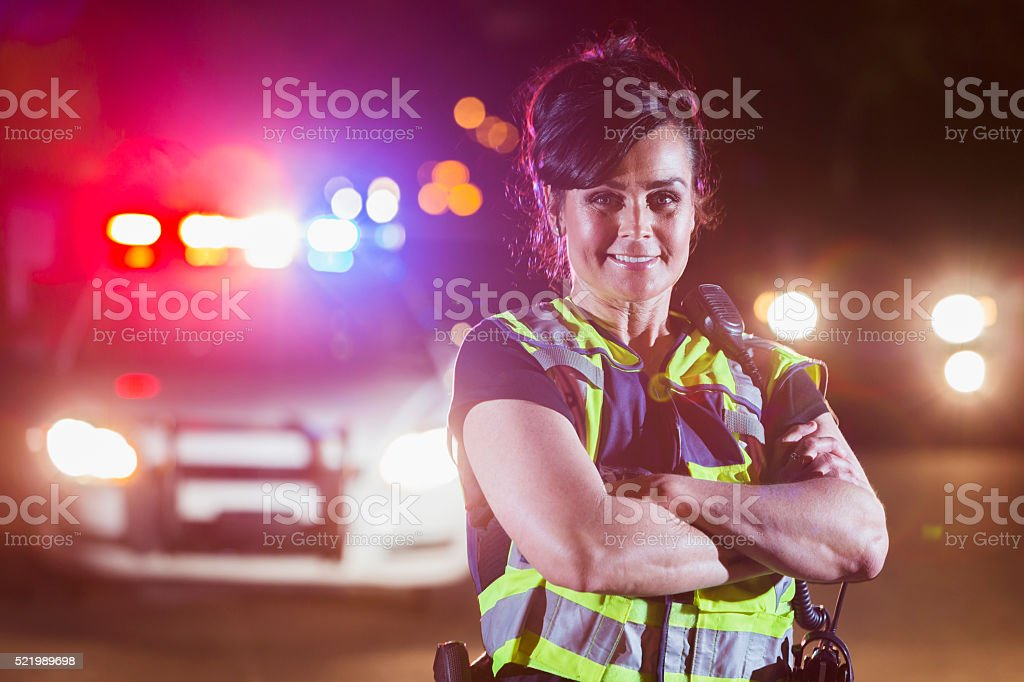 Female police officer at night, lights on patrol car stock photo