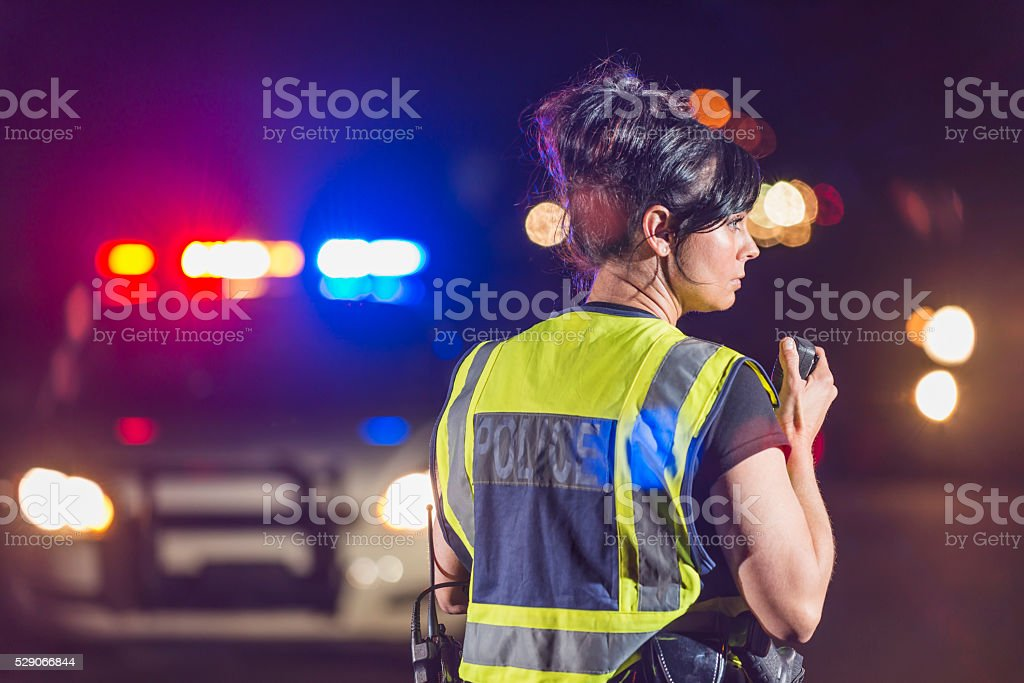 Female police officer at night, talking on radio stock photo