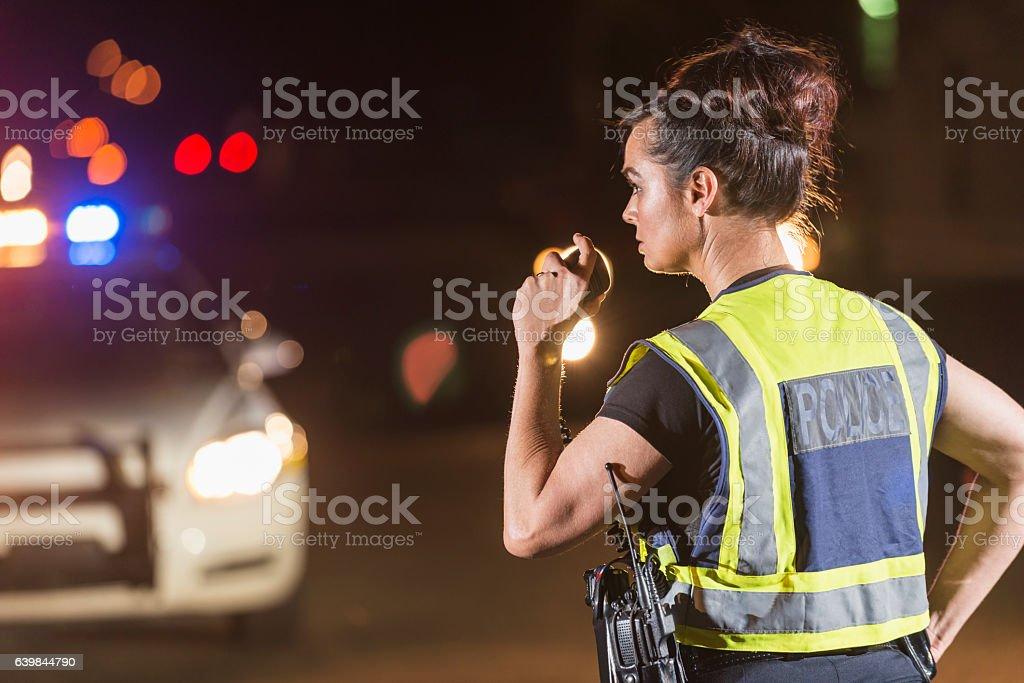 Female police officer at night, talking on radio stock photo