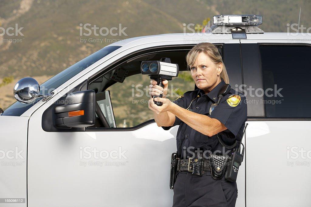 Female Police Officer checking vehicle speed with radar gun stock photo