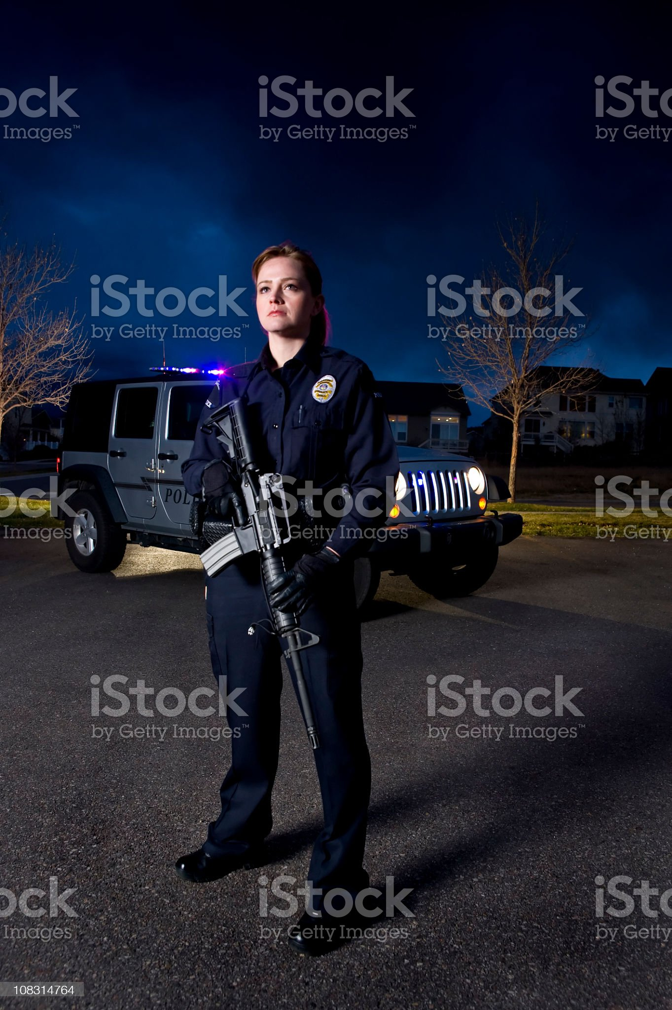 Female Police Officer in Suburban neighborhood with assault rifle royalty-free stock photo