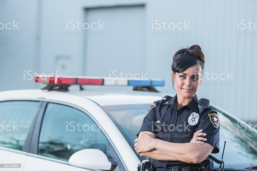 Female police officer standing next to patrol car stock photo
