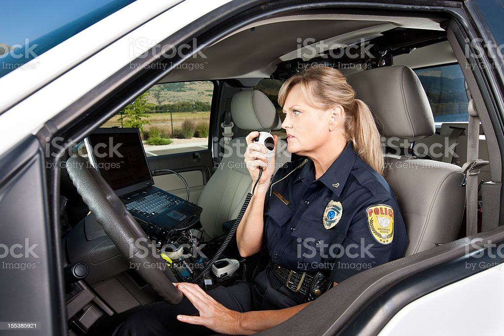 Female Police Officer Talking on Radio in Vehicle stock photo