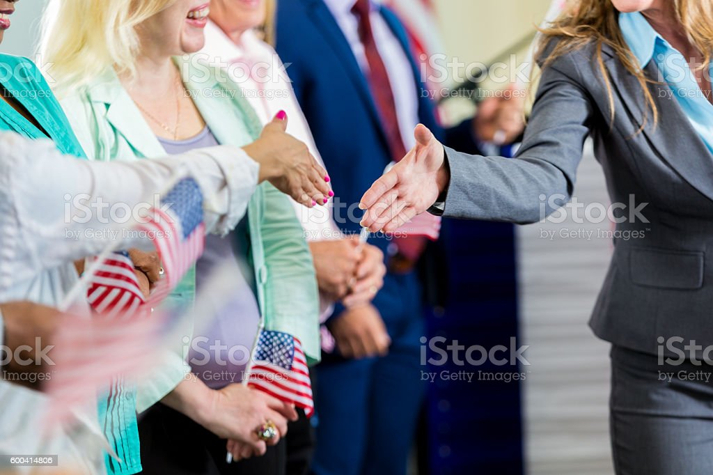 Female politician shaking hands with supporters at event stock photo