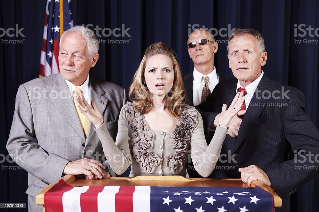 Female politician with three male security personnel on a campaign stock photo
