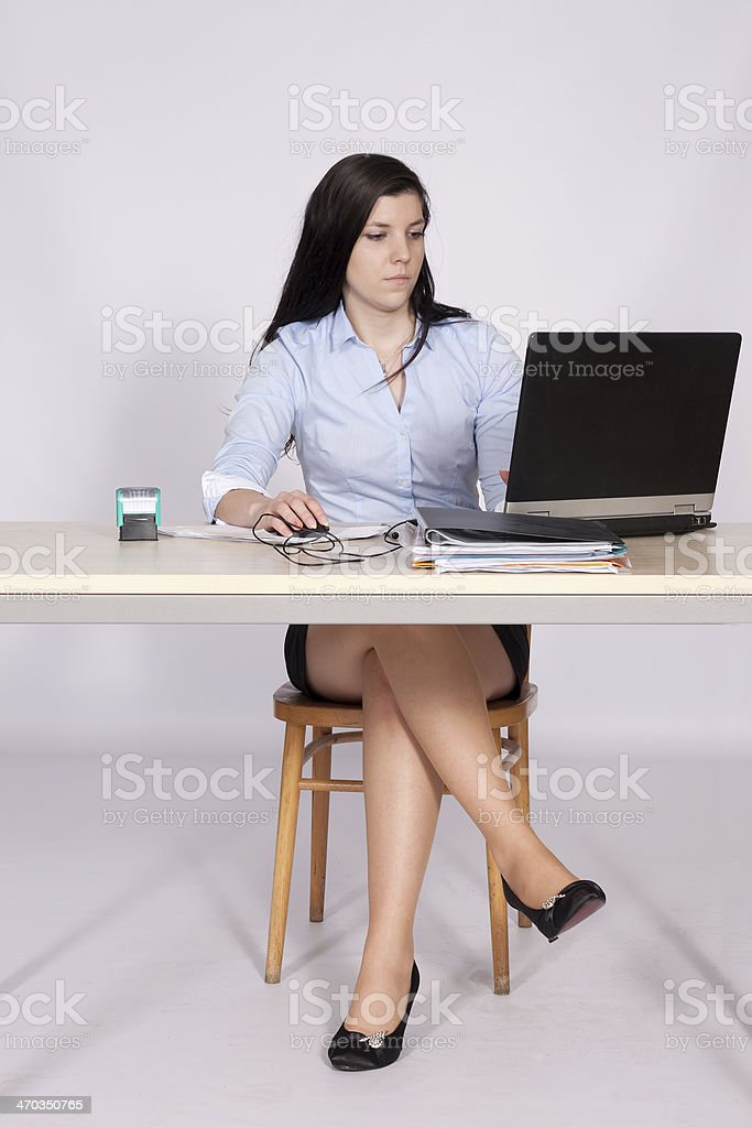 Female poses behind a desk in the office stock photo