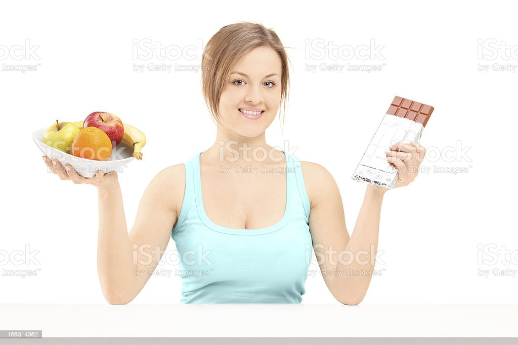 Female posing with a bowl of fruit and chocolate royalty-free stock photo