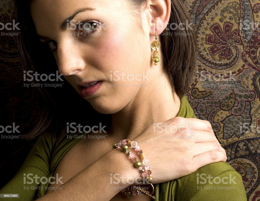 Female Posing With Jewelry Against Tapestry stock photo