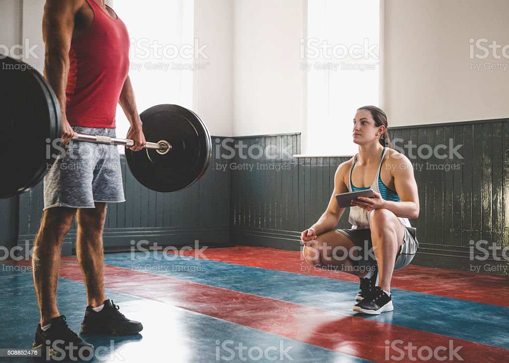 Female Powerlifter Personally Training a Client stock photo