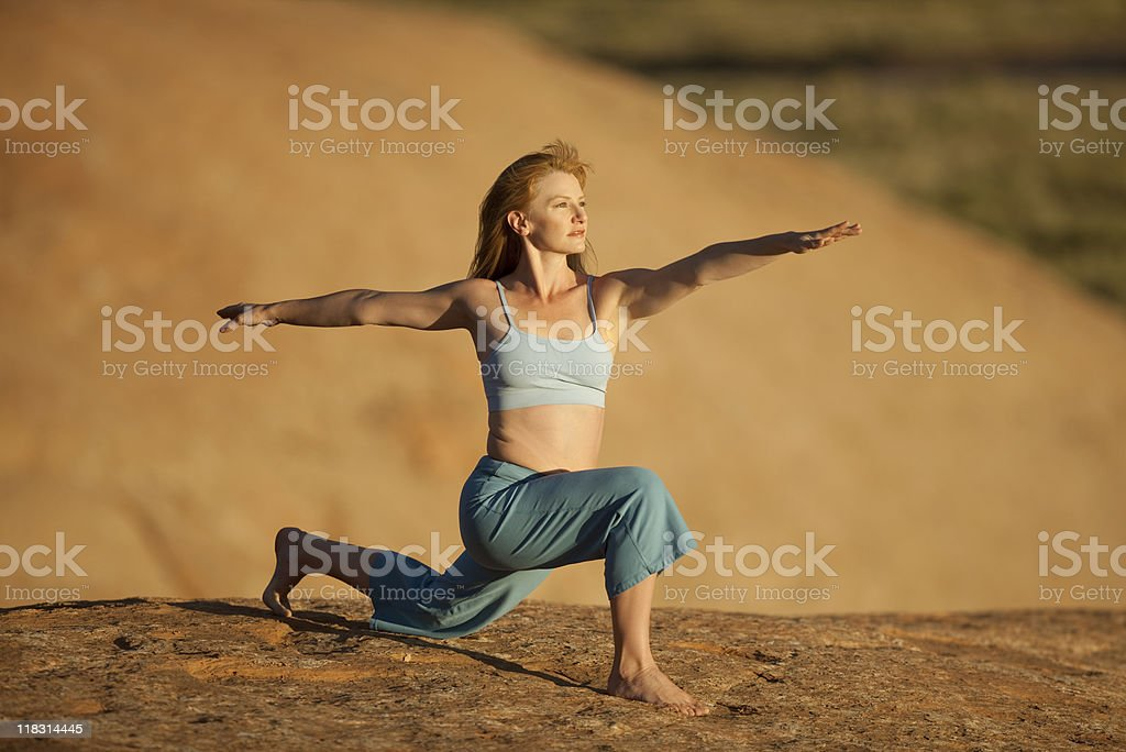 Female Practicing Yoga In Warrior 2 Pose royalty-free stock photo