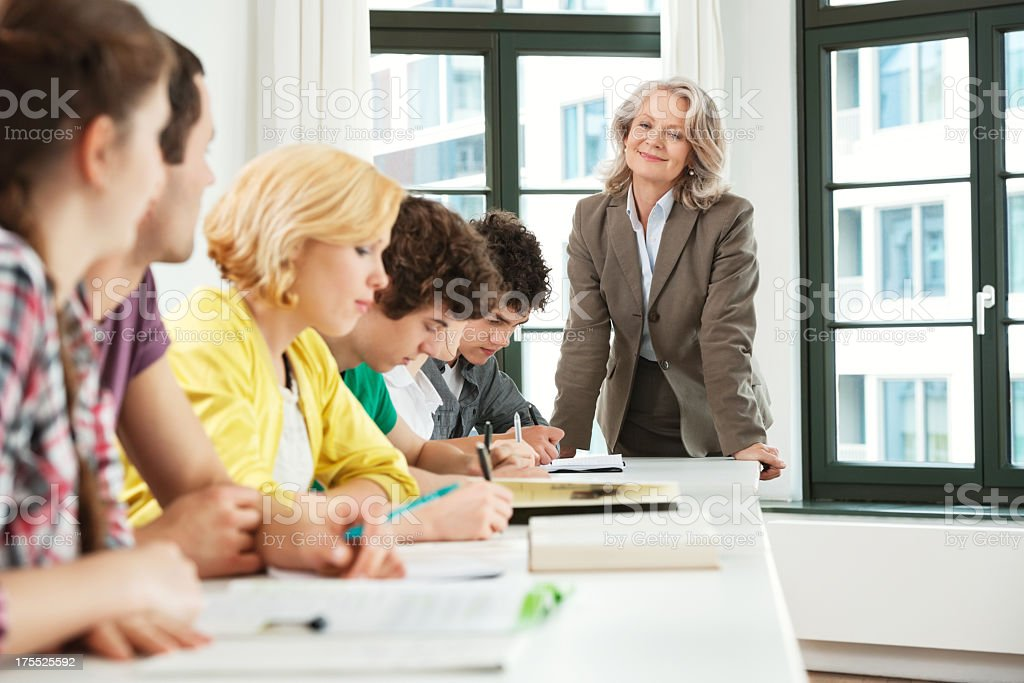Female Professor Looking At Students During Class Hours royalty-free stock photo
