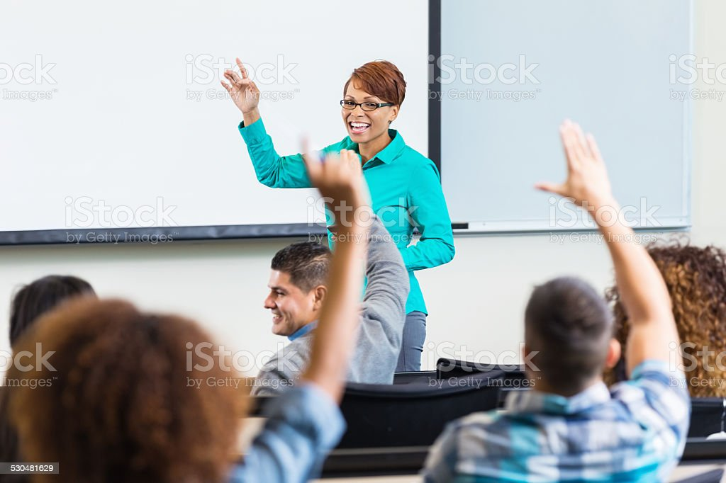 Female professor taking questions after lecture in college classroom stock photo